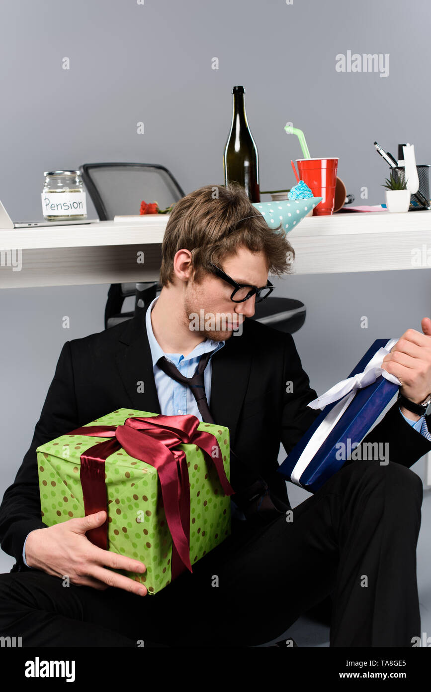 drunk businessman in party cap looking at presents at workplace - Stock Image