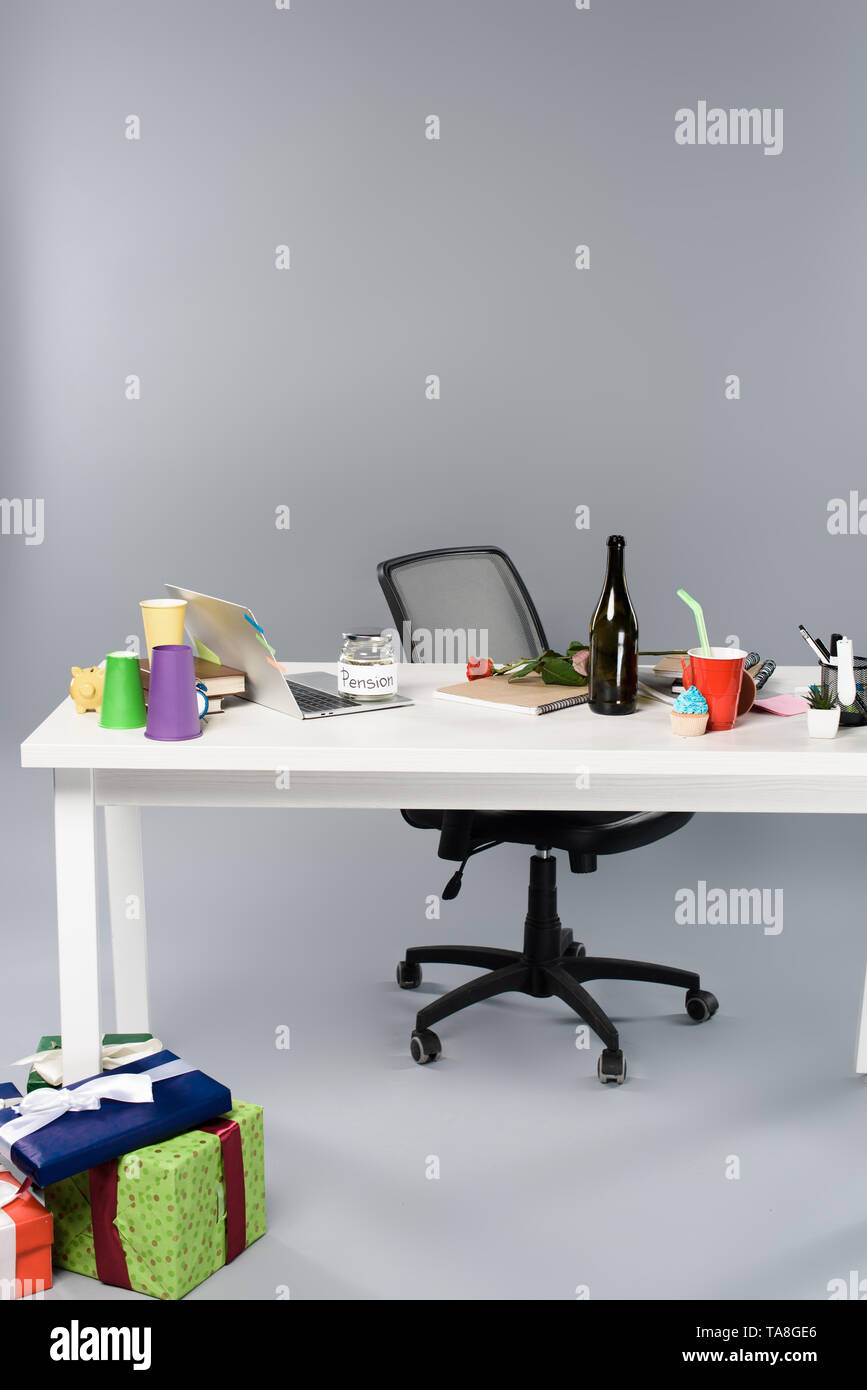 messy workplace with champagne bottle, paper cups, pension moneybox and laptop on white table near gift boxes - Stock Image