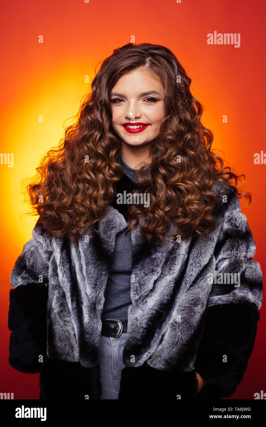 Curly headed teenager. Teenage girl with stylish wavy hairstyle. Pretty girl with curly hairstyle. Young woman with long locks of hair. Healthy hair - Stock Image