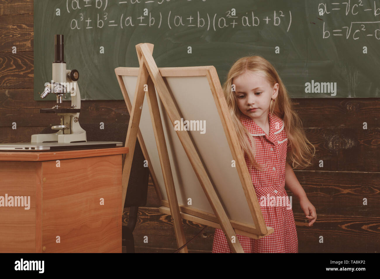 Cute girl artist painting picture on canvas on easel. Little child learn drawing on studio easel, vintage filter. - Stock Image
