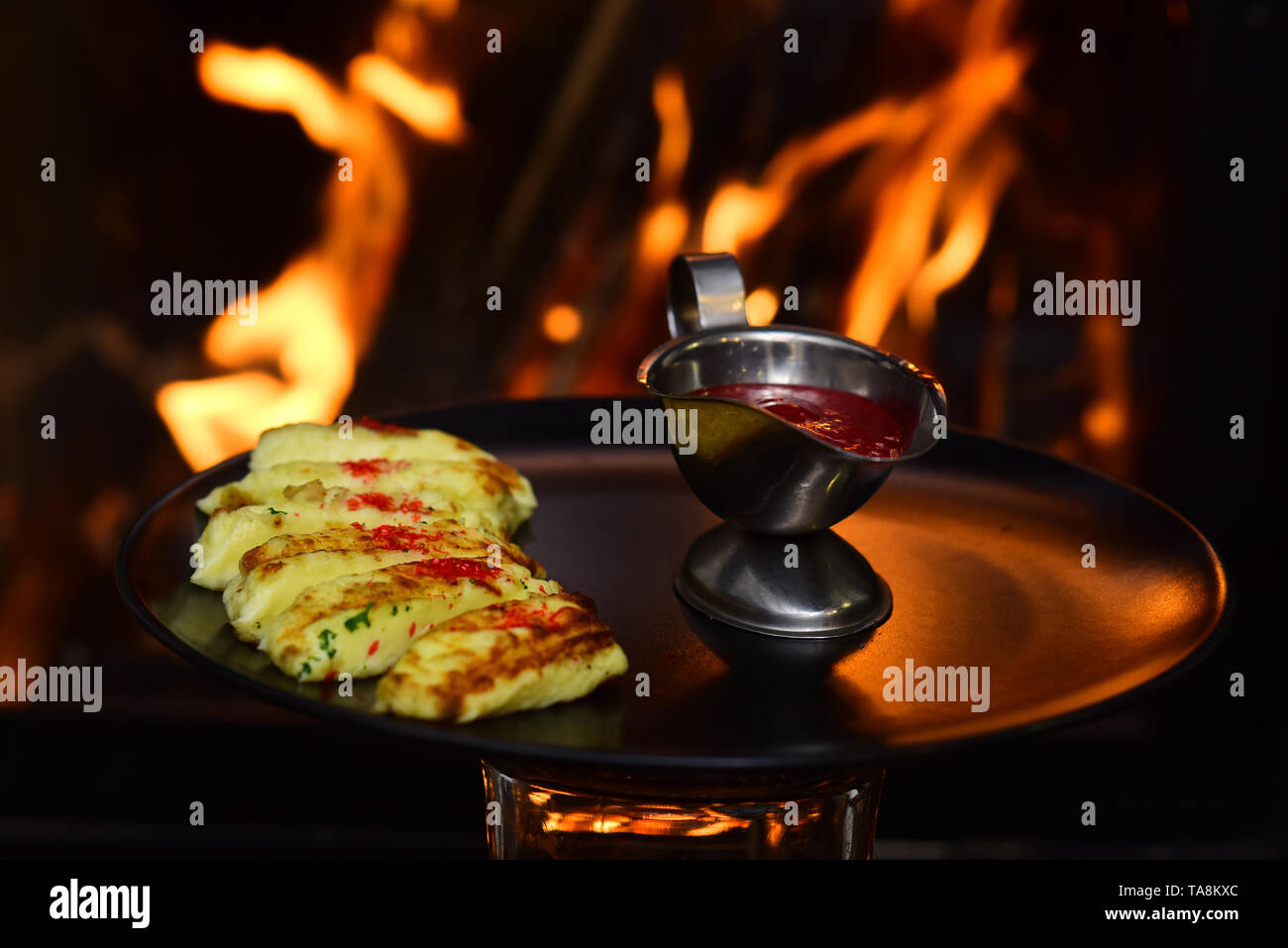 Dip sauce served to food item on burning fire background. Red fruit berry dip in saucepan. It is never too spicy - Stock Image