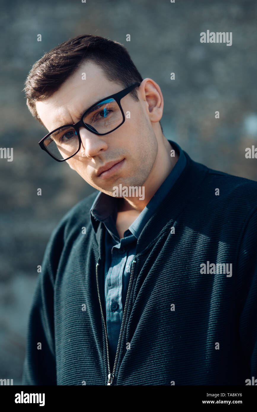 20bca3ede2bc Portrait of man wearing spectacles and looking at camera outdoor. Man with  glasses feeling confident