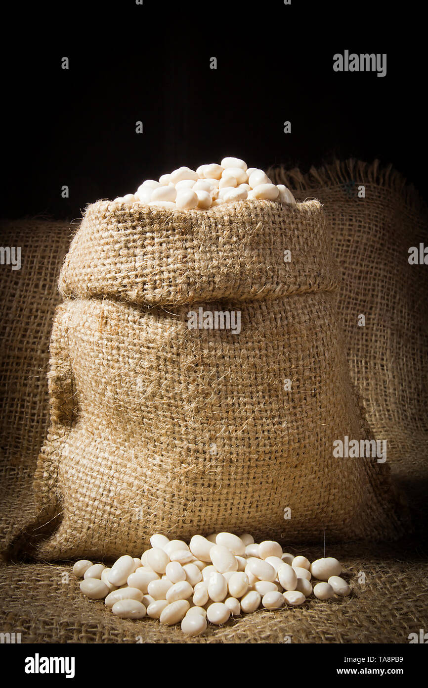 Beans in a bag on the background of burlap - Stock Image