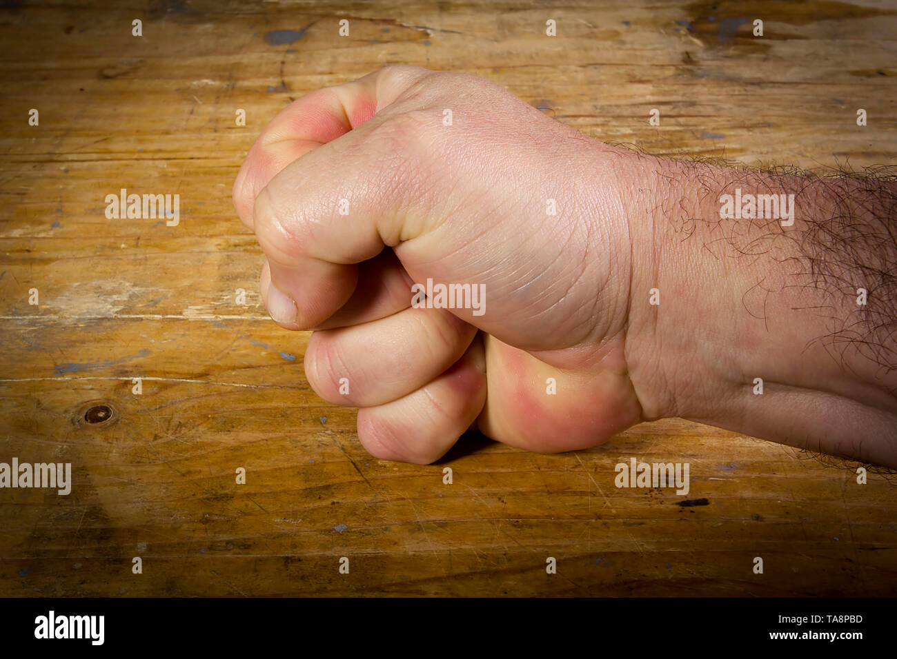 Male hand clenched into a fist on a wooden table. Stock Photo