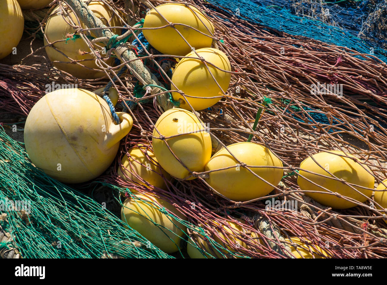 Old fishing nets in a heap under Mediterranean sunshine - Stock Image