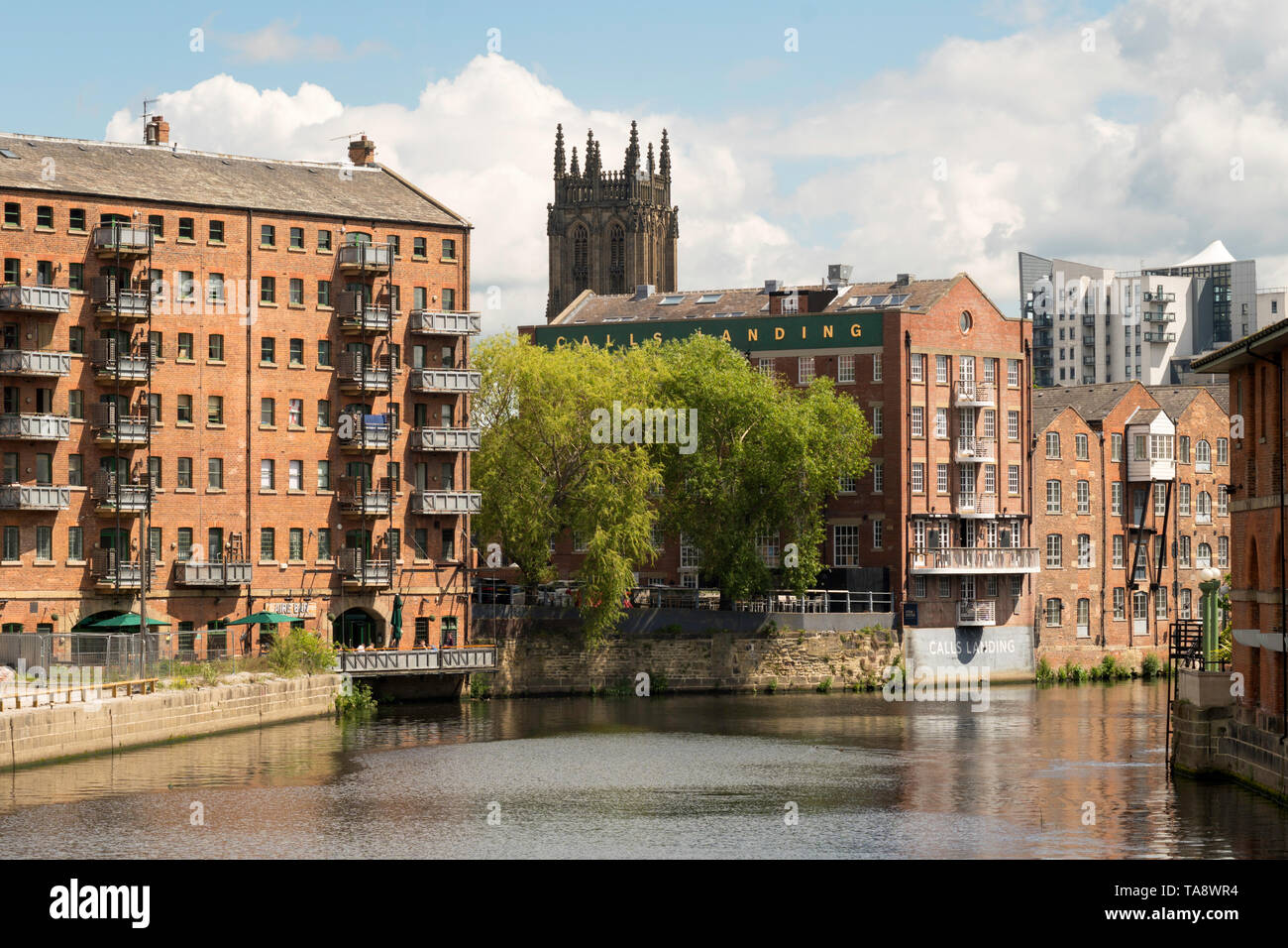 Warehouses converted into offices and apartments along the river Aire in  Leeds, Yorkshire, England, UK - Stock Image