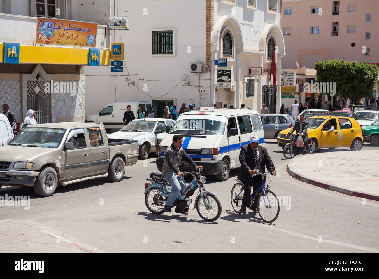 TUNISIA-CIRCA MAY, 2012: Road traffic is on the streets of Tunisian provincial town. Passengers cars, motorcycles and bikes drive on roundabout roadwa Stock Photo