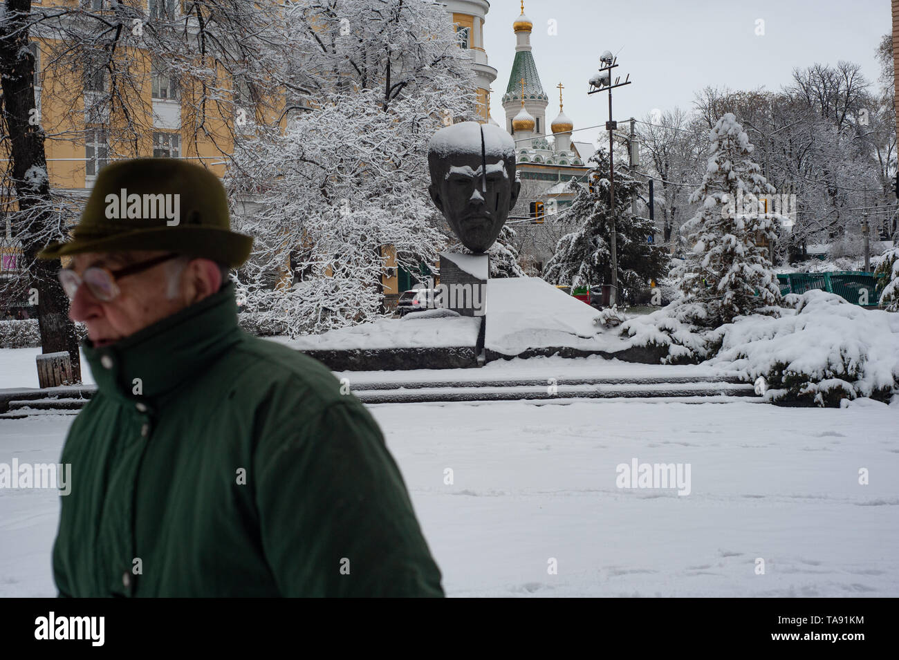 An Old Bulgarian man walks past the Stefan Stambolov Monument, in the snow of Crystal Park, Sofia, Bulgaria, Europe - Stock Image