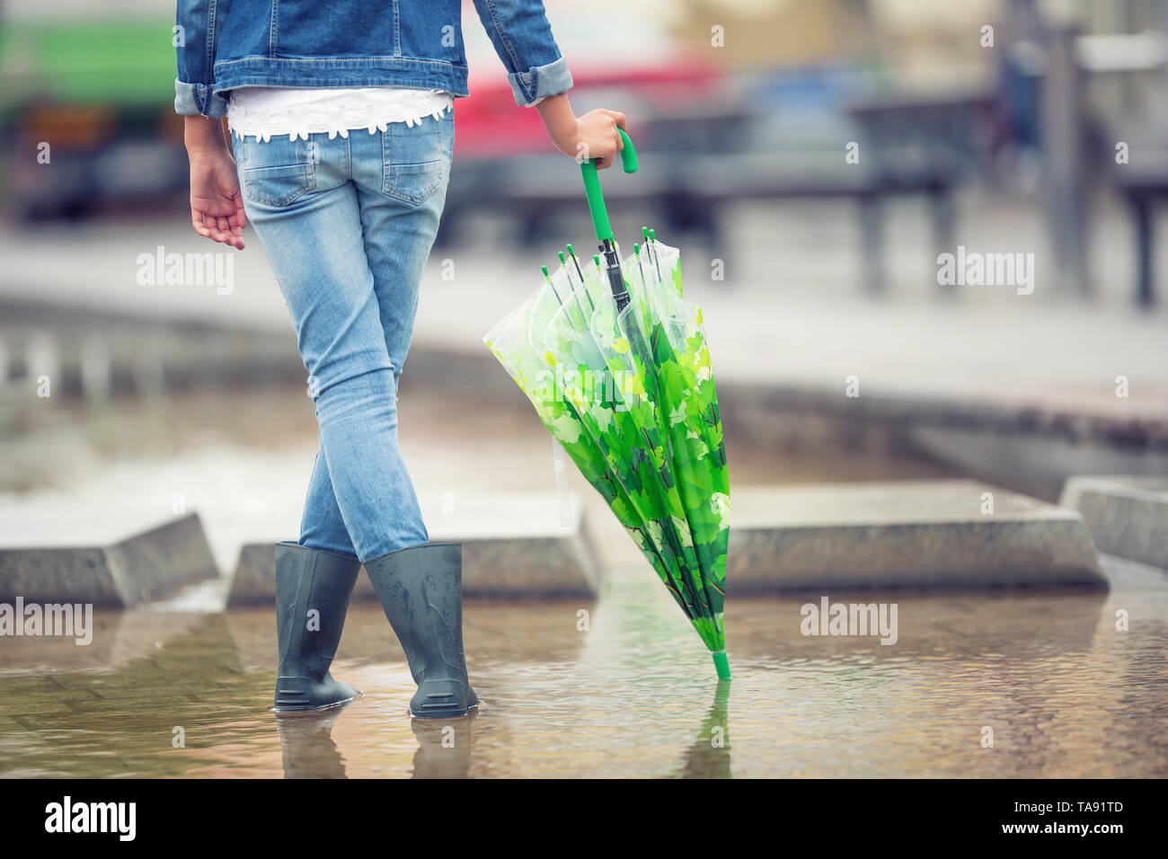 Young pre-teen girl stands with an umbrella in puddle after spring or summer rain. - Stock Image