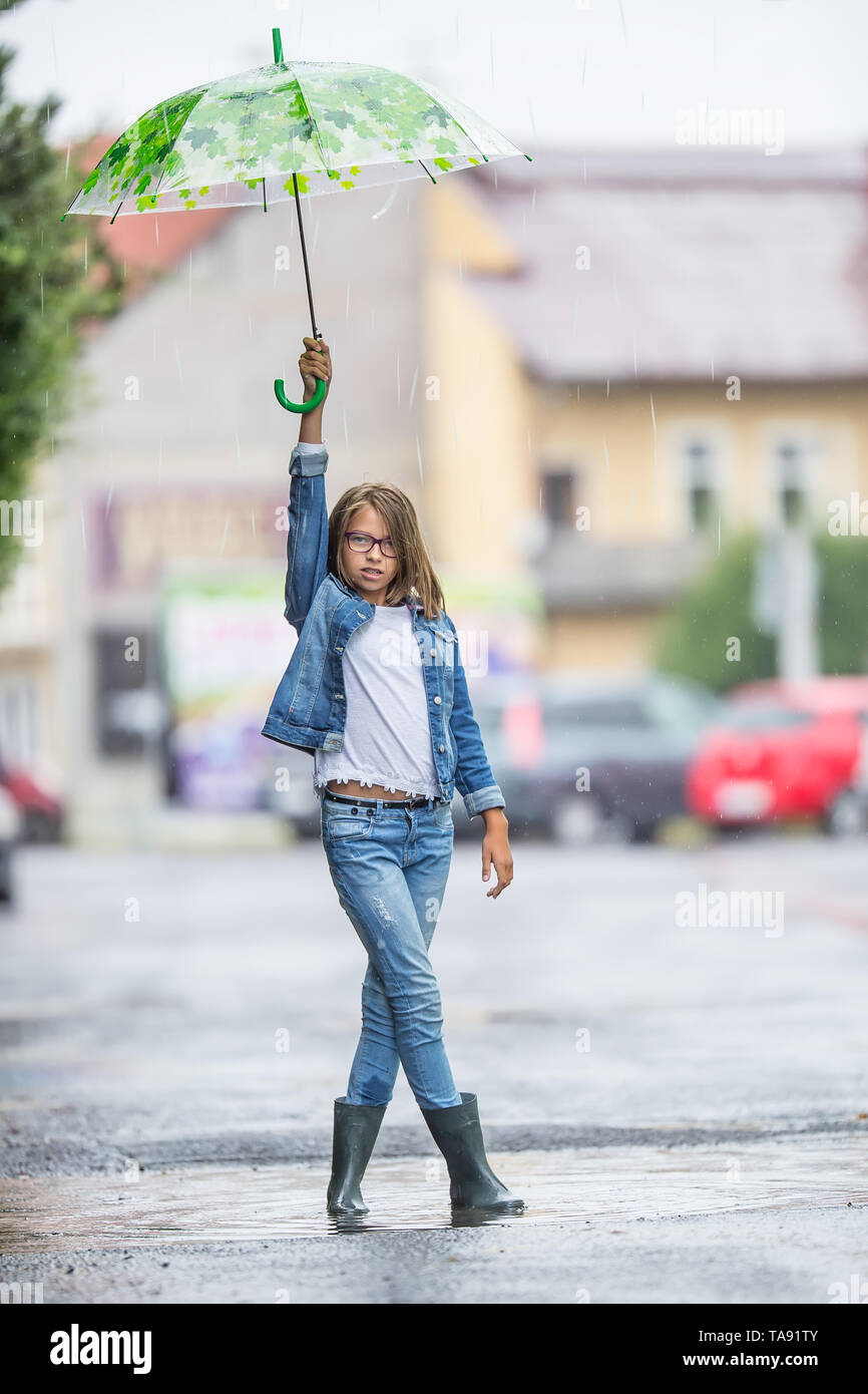 Portrait of beautiful young pre-teen girl with umbrella under spring or summer rain. - Stock Image