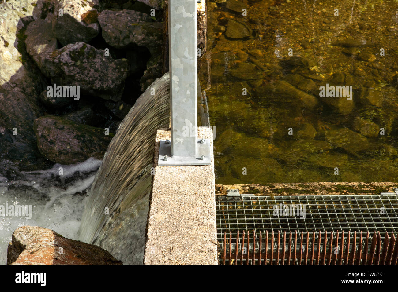 Spillway over a small dam close up. Water level difference. Regulation of the water level in the lake. Stock Photo