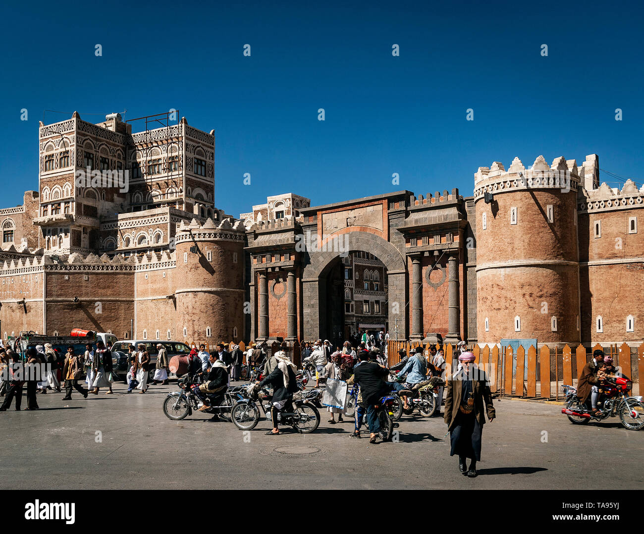 street scene and local heritage architecture buildings in old town of sanaa yemen at Bab Al Yemen gate - Stock Image