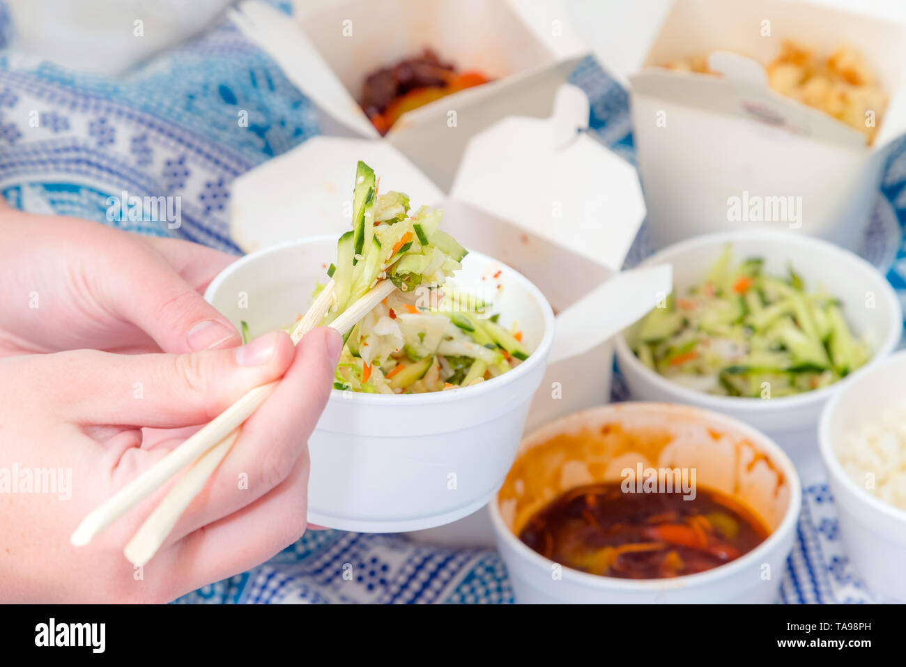 Eating Chinese take away food with chop sticks at home with bed sheets in the background. Spicy asian food in white box - salad, souse, rice with egg, - Stock Image