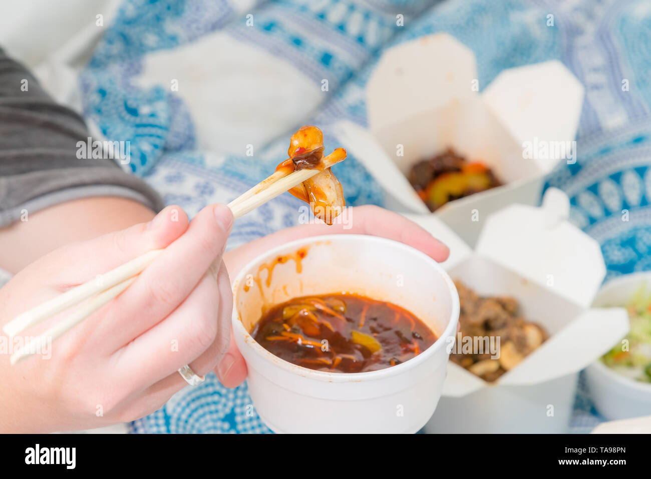 Eating Chinese take away food with chop sticks at home with bed sheets in the background. Spicy asian food in white box - salad, souse, beef, chicken  - Stock Image