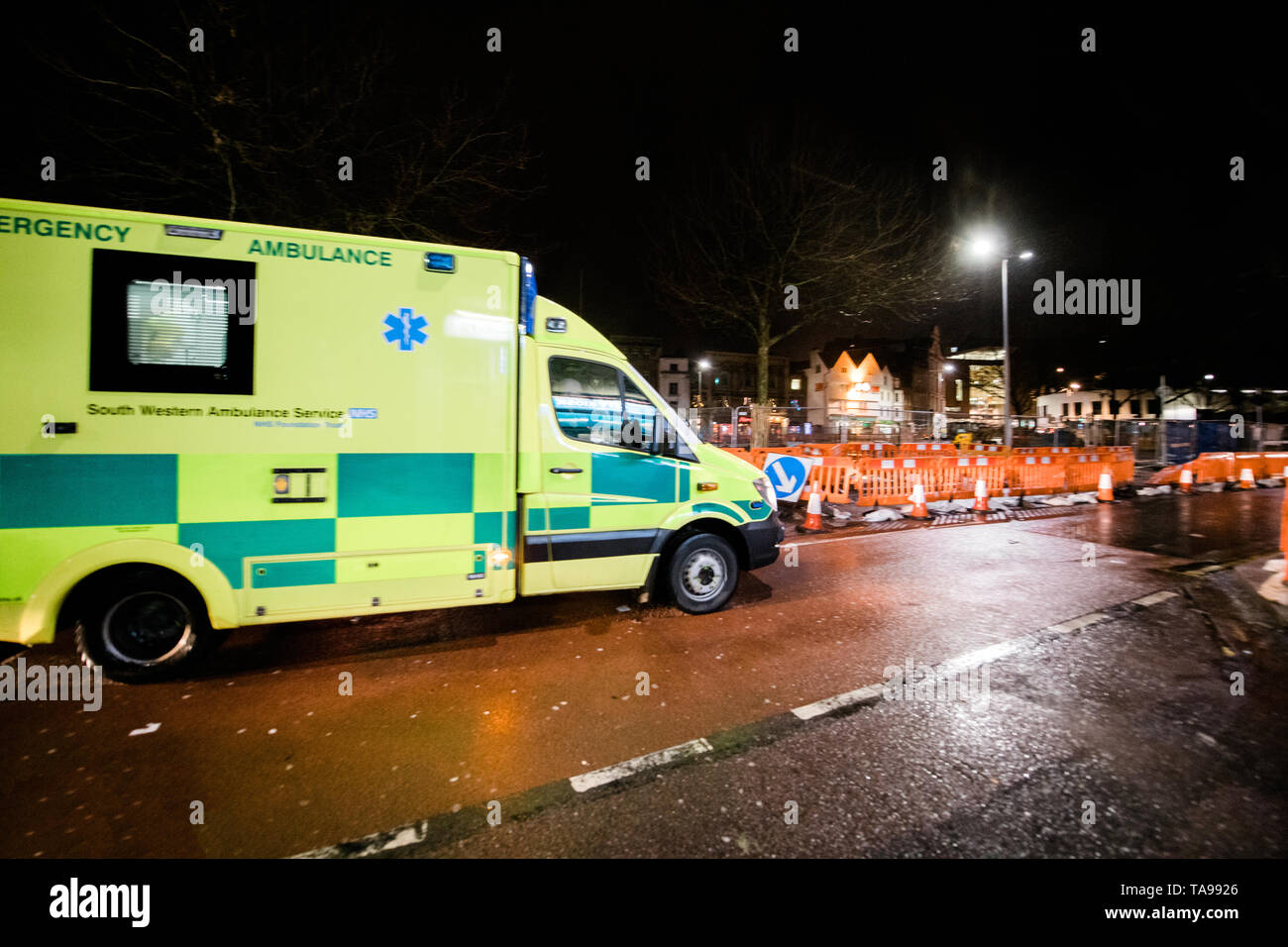 London, United Kingdom - Mar 5, 2017: Yellow NHS ambulance driving fast on the repaired with roadworks street in central london at night  - Stock Image