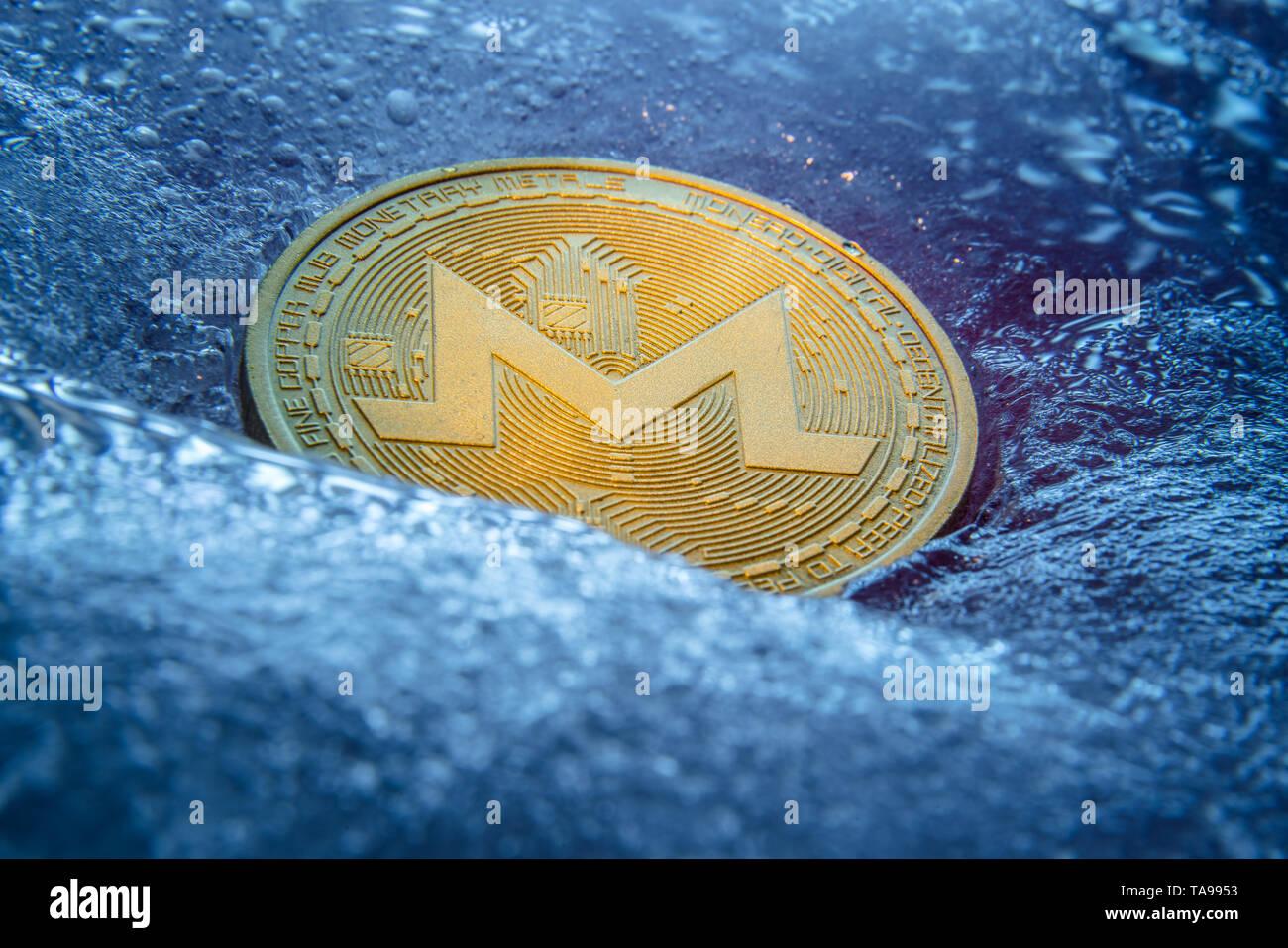 Golden Monero coin, online digital currency frozen in the blue ice. Concept of block chain, crypto market crash. Frozen crypto money, depreciation - Stock Image