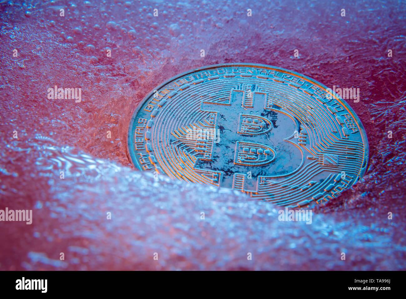 Silver Bitcoin, bit coin online digital currency frozen in the blue ice. Concept of block chain, crypto market crash. Frozen crypto money, depreciatio - Stock Image