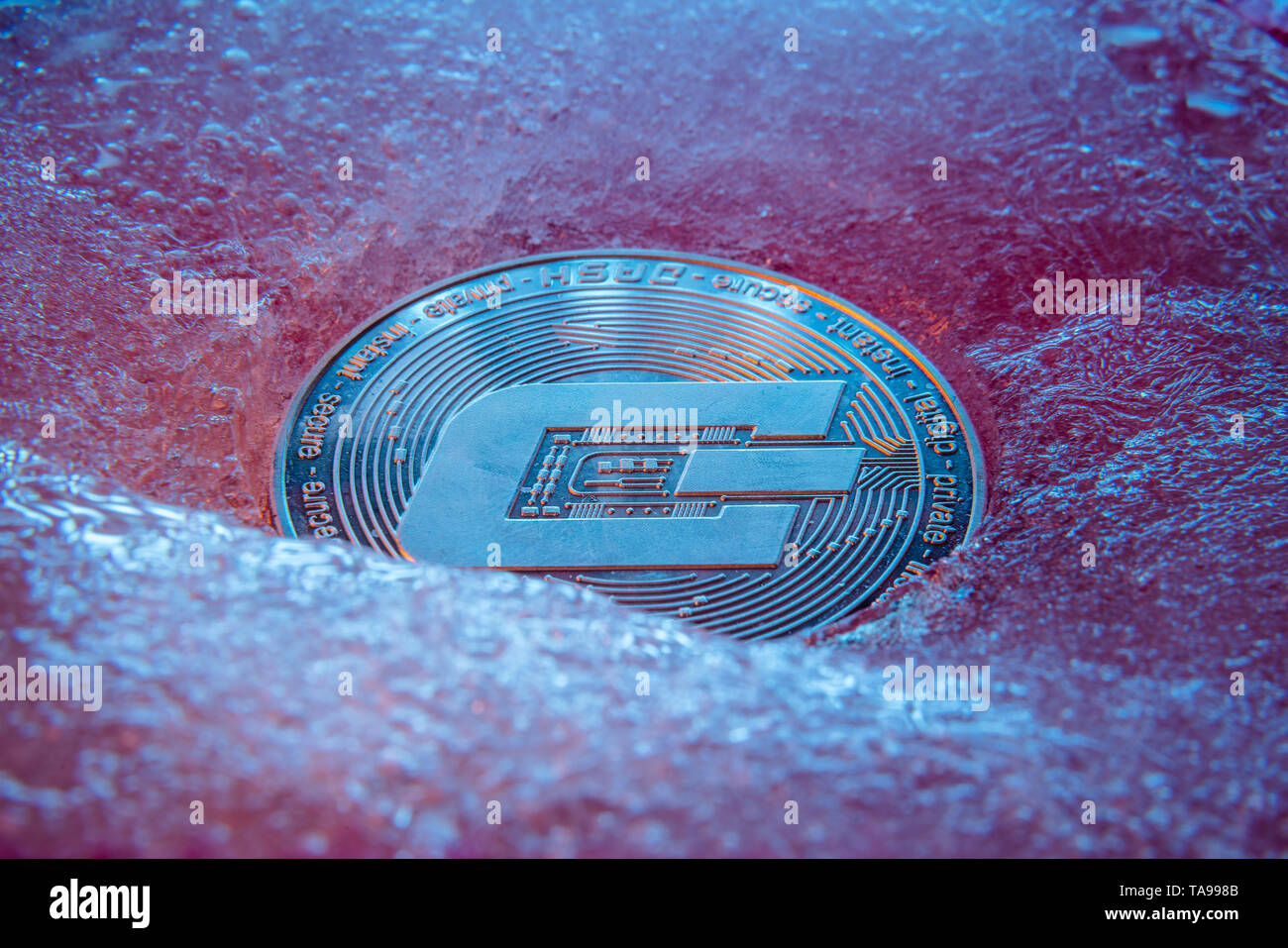 Silver Dash coin, online digital currency frozen in the blue ice. Concept of block chain, crypto market crash. Frozen crypto money, depreciation - Stock Image