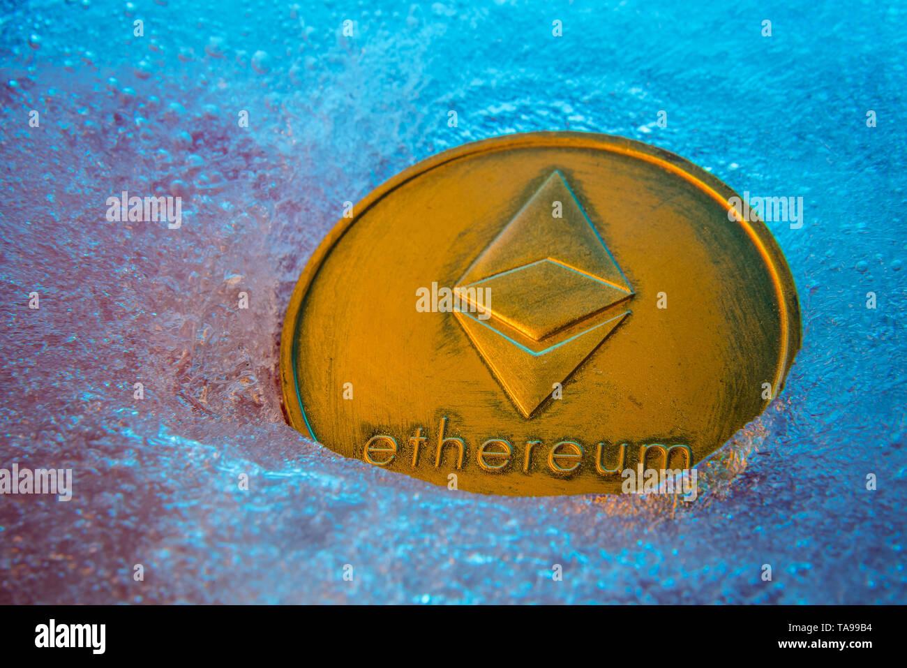Golden Ethereum coin, online digital currency frozen in the blue ice. Concept of block chain, market crash. Frozen crypto money, depreciation - Stock Image