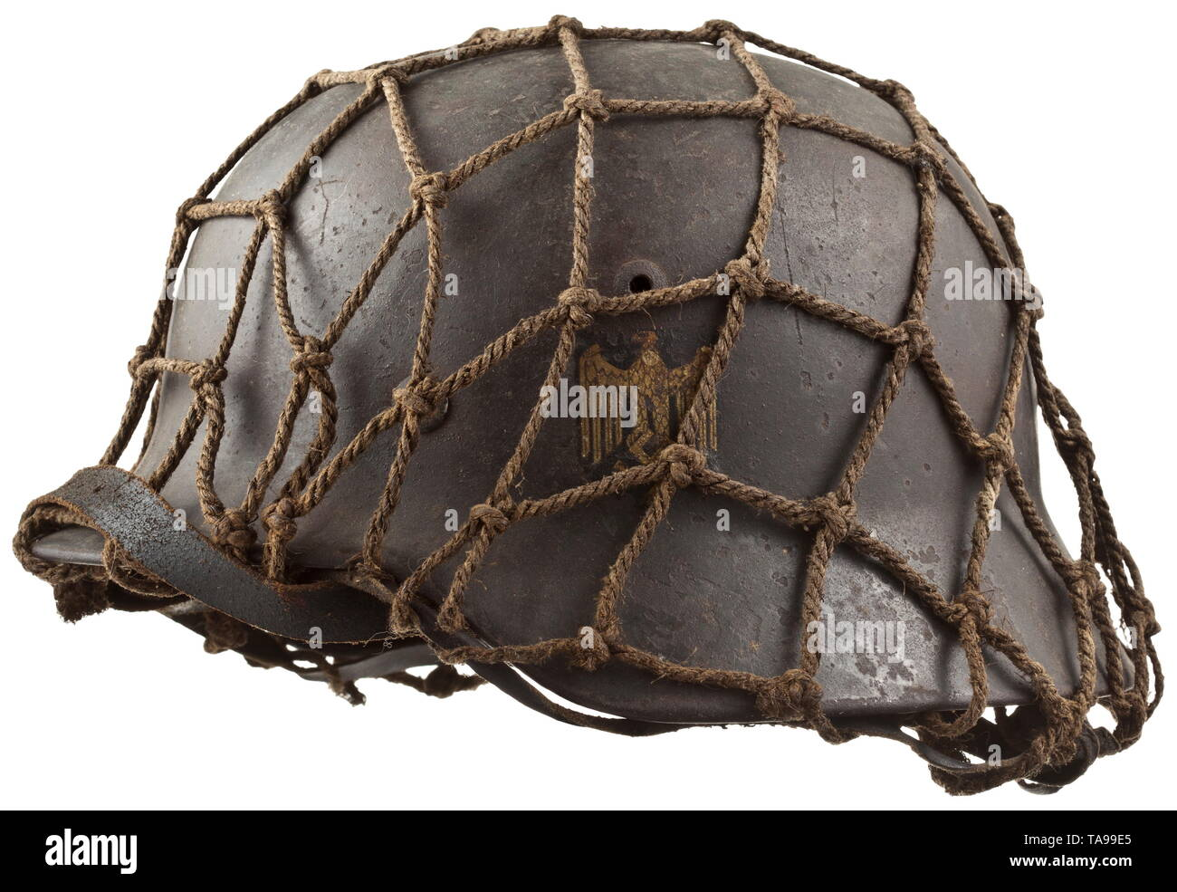 A steel helmet M 40 with camouflage netting Steel skull with light, rough camouflage paint, the national emblem nearly completely intact, the inside with maker stamping 'ET62' (Thale Iron Works) and '4097', netting stretched for affixing further camouflage material, intact inner liner with chin strap. historic, historical, army, armies, armed forces, military, militaria, object, objects, stills, clipping, clippings, cut out, cut-out, cut-outs, 20th century, Editorial-Use-Only - Stock Image