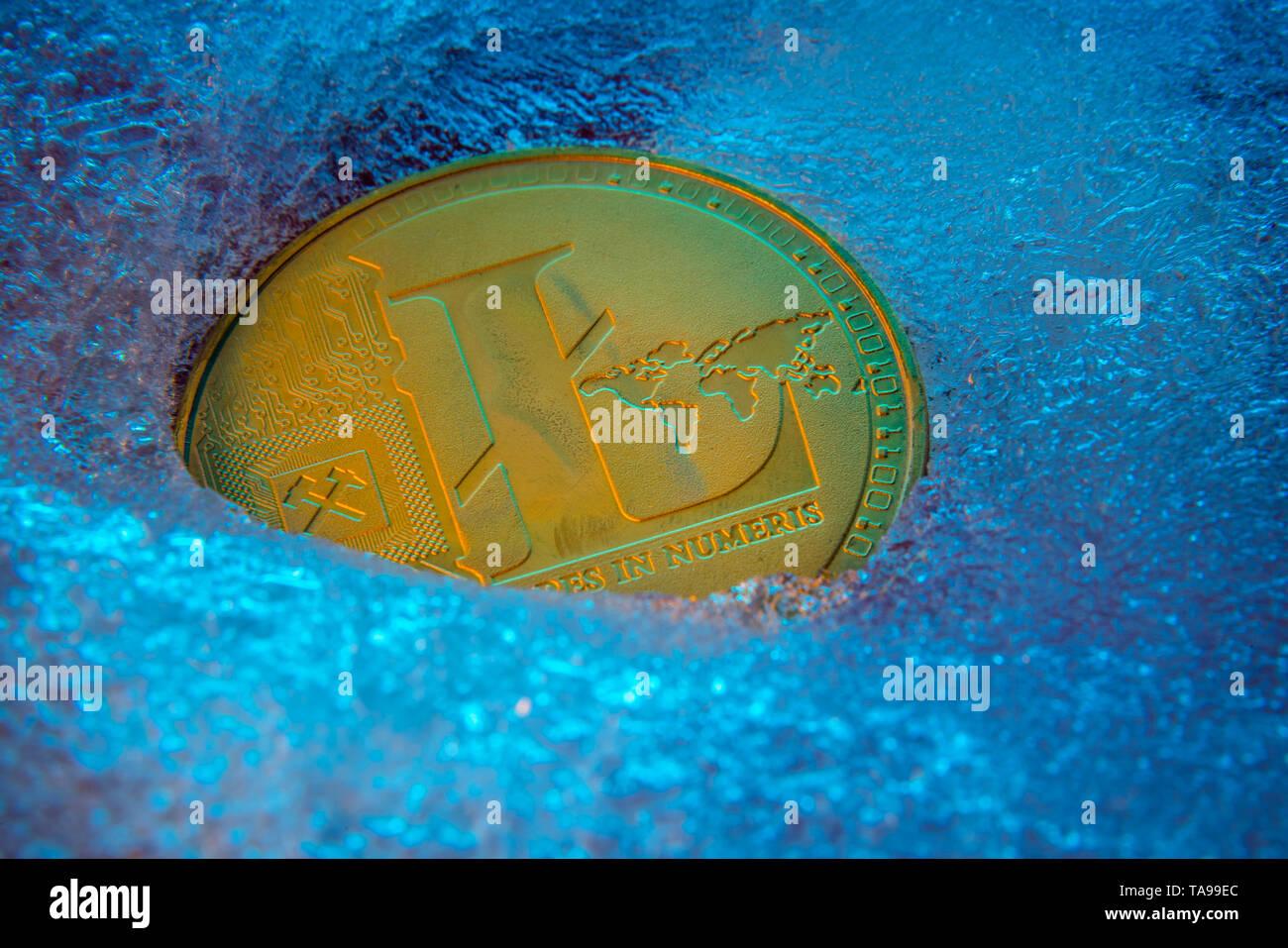 Golden Litecoin coin, lite coin online digital currency frozen in the blue ice. Concept of block chain, market crash. Frozen crypto money, depreciatio - Stock Image
