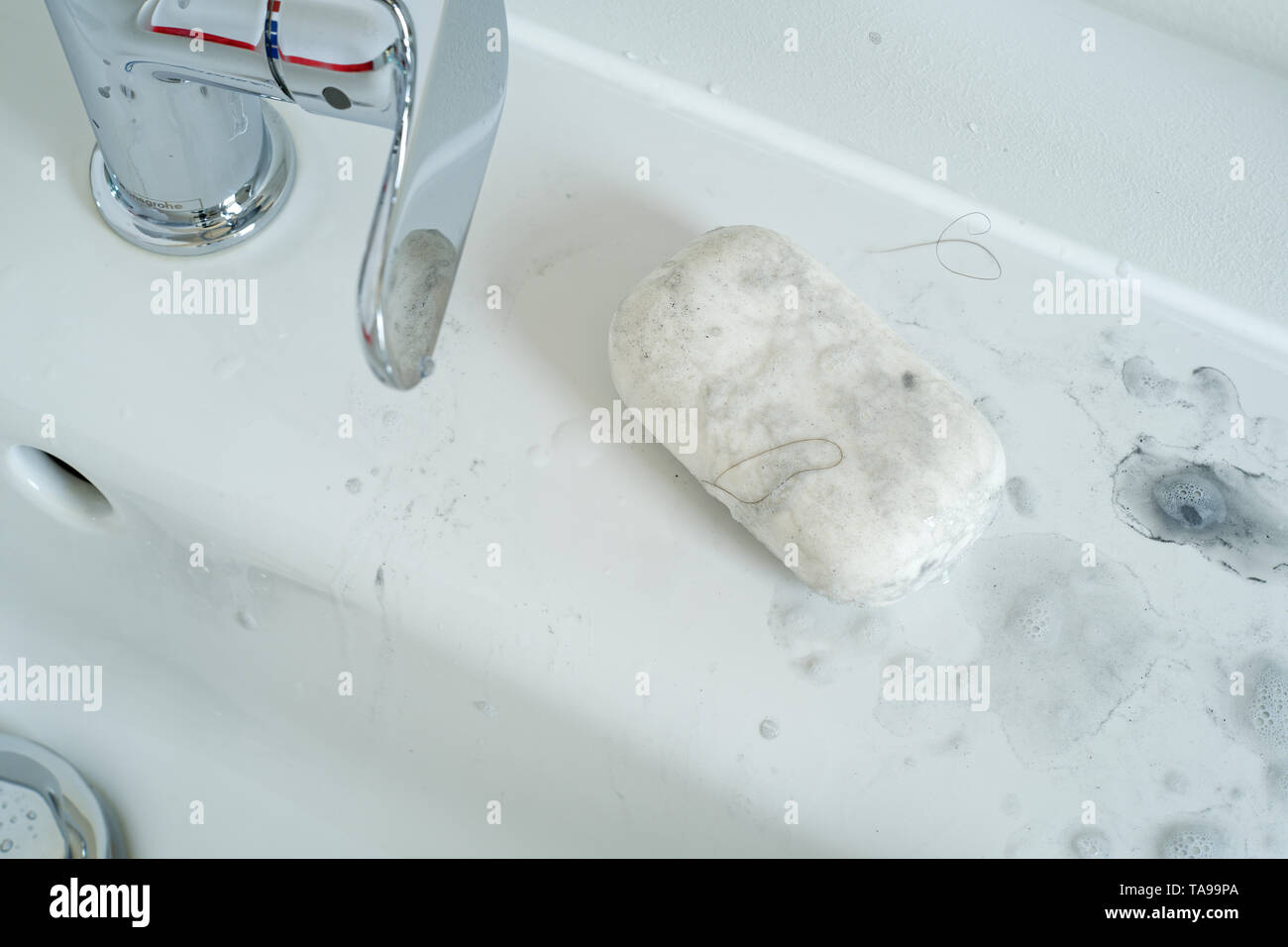 Dirty soap used to clean of heavy dirt and grease by the side of a sink. - Stock Image