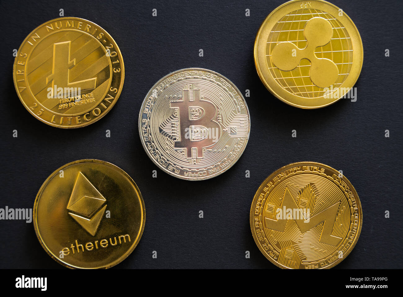 Main crypto currency coins next to each other: Bitcoin, Litecoin, Ripple, Monerd, Ethereum coin on black background. Digital currency, block chain mar - Stock Image