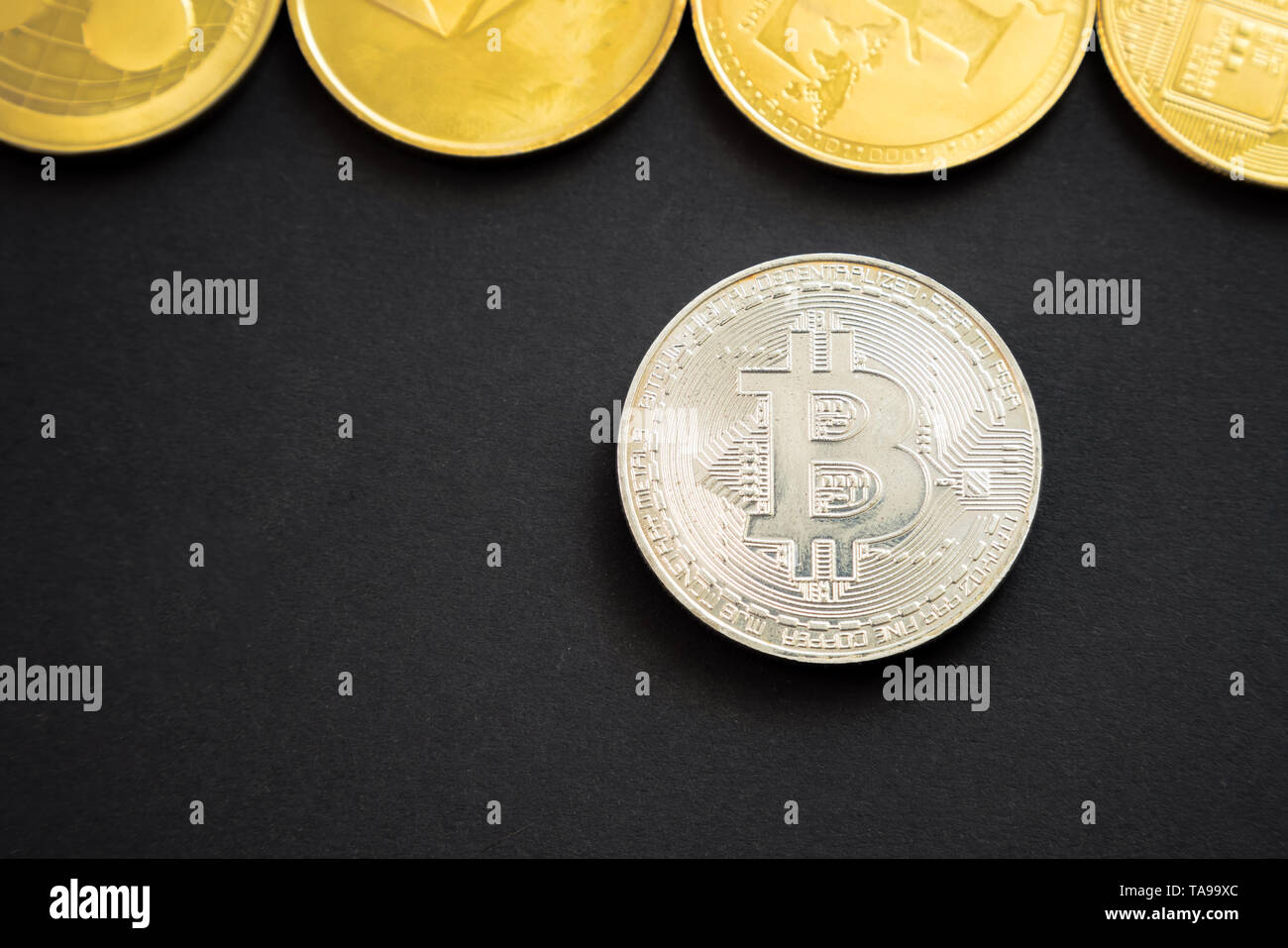 Silver bitcoin crypto currency coin next to others: Litecoin, Ripple, Monerd, Ethereum coin on black background. Digital currency, block chain market - Stock Image