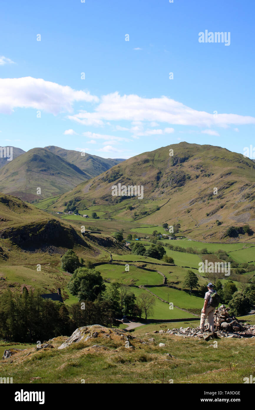View south from southern slopes of Hallin Fell in Lake District, Cumbria with male walker looking at view over Martindale to The Nab and Beda Fell. Stock Photo