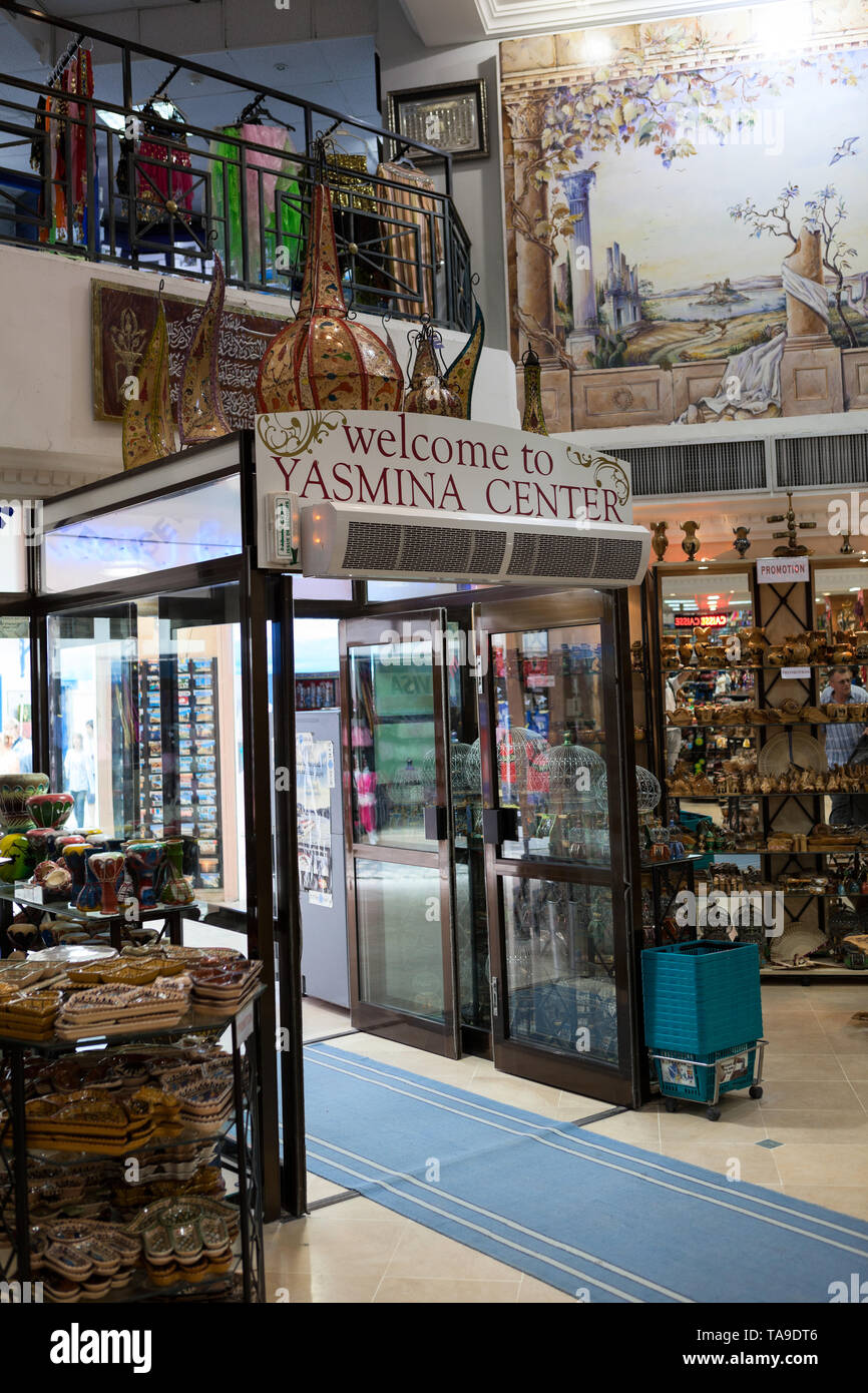 SOUSSE, TUNISIA-CIRCA MAY, 2012: Entrance door and interior of Yasmina souvenir center. Interior of large giftshop with lot of advertising gifts and n - Stock Image