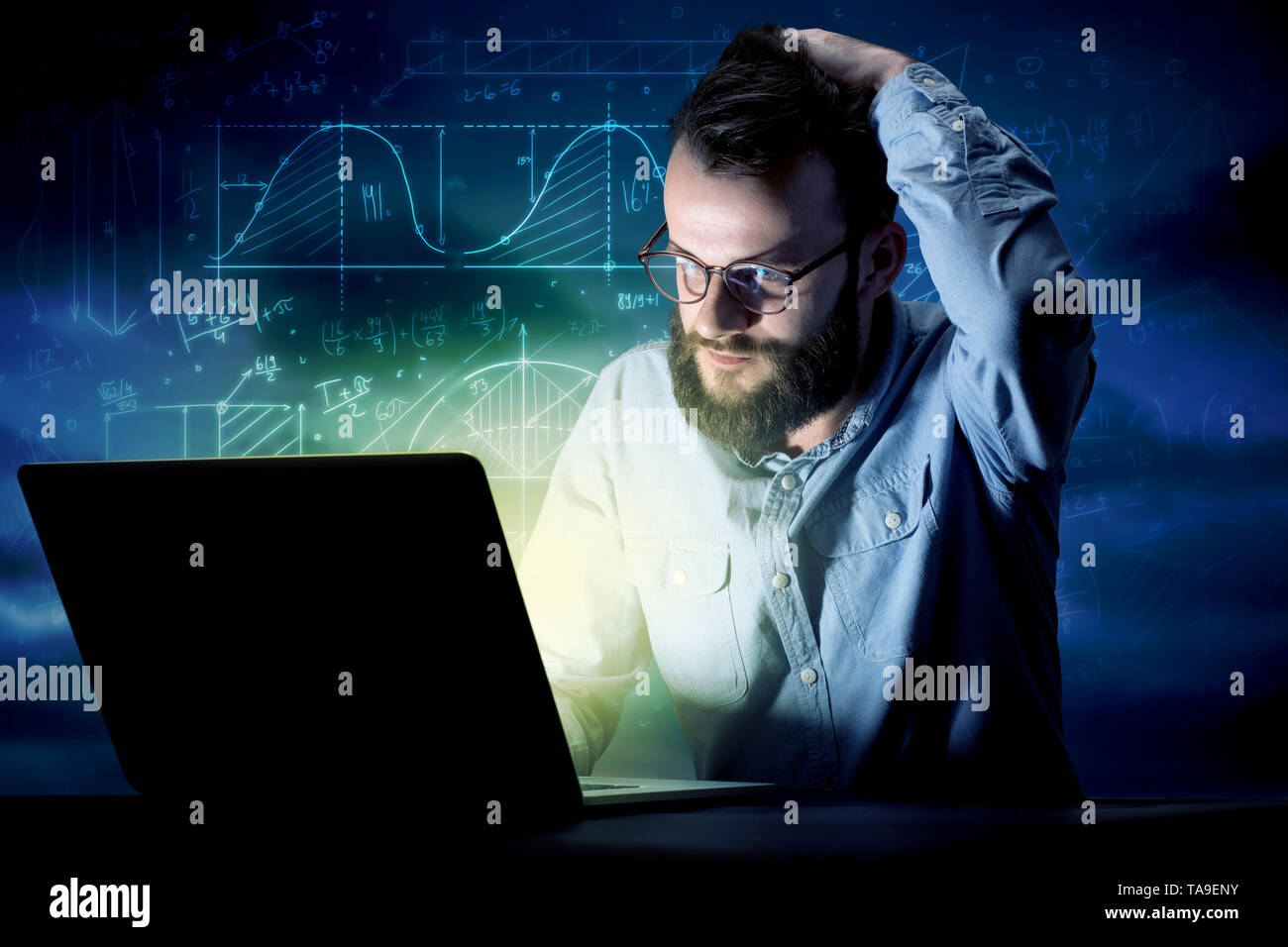 Young handsome businessman working late at night in the office with blue mathematic charts in the background - Stock Image