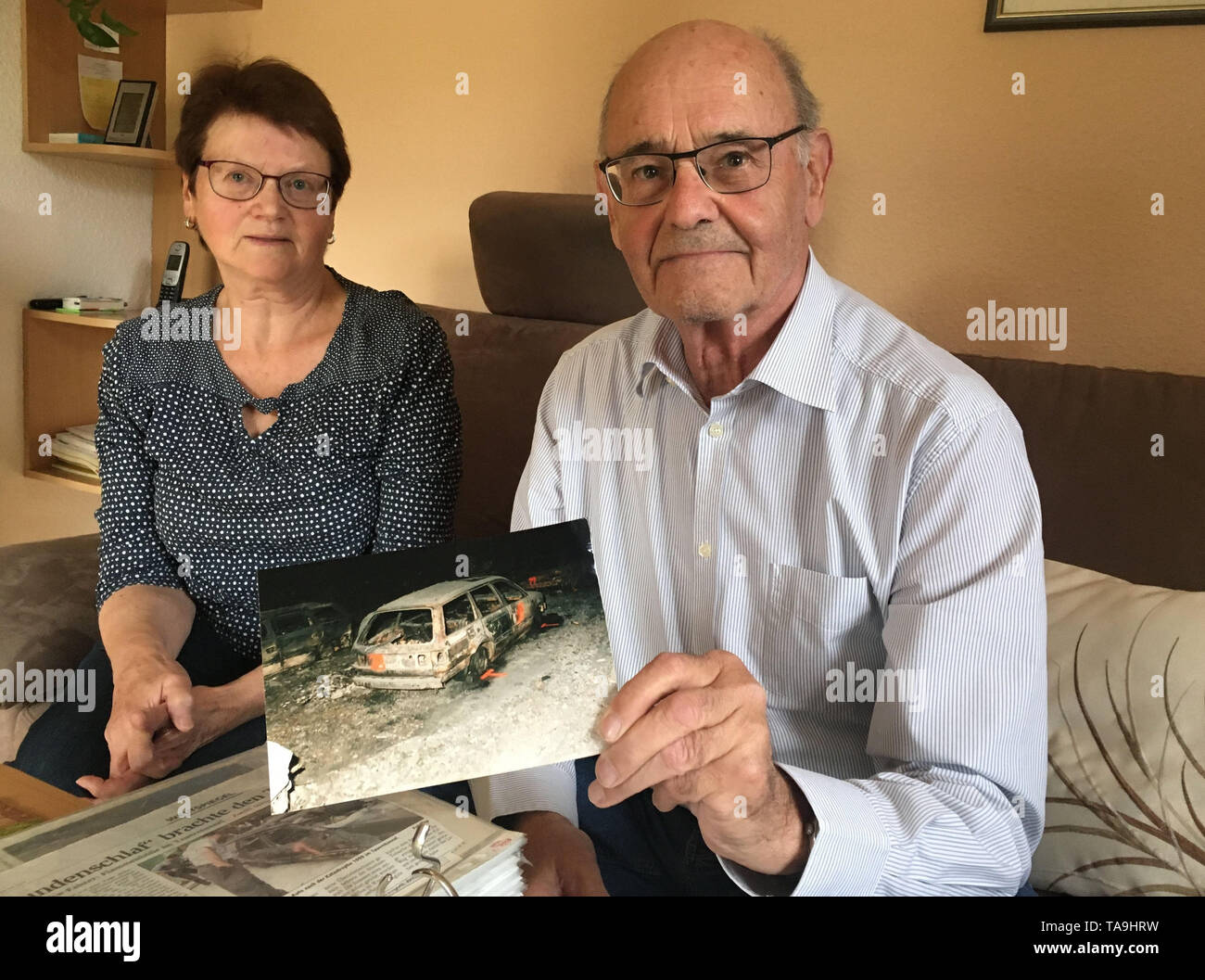 Teisendorf, Germany. 15th May, 2019. The married couple Ludwig and Eva Mayer from Teisendorf in Upper Bavaria. Ludwig Mayer (77) holds a photo of his VW Passat, which burned out in the Tauern tunnel catastrophe. 71-year-old Eva Mayer is still afraid of trucks today. They were among the survivors of the accident which claimed twelve lives and injured 48 on 29 May 1999. (to dpa ' Barefoot from the hell of flames - Inferno in the Tauern tunnel had consequences') Credit: Matthias Röder/dpa/Alamy Live News - Stock Image