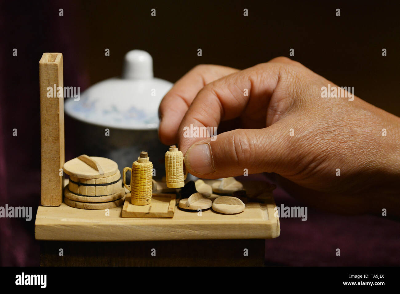 Beijing, China's Jiangsu Province. 21st May, 2019. Chen Hesheng puts a finger-sized wooden thermos bottle on the miniature model of cooking stove in Nanjing, east China's Jiangsu Province, May 21, 2019. Chen Hesheng, a 70-year-old carpenter, has made about 170 miniature models of antique articles including agricultural equipment and daily necessities over the past decade. Credit: Fang Dongxu/Xinhua/Alamy Live News - Stock Image