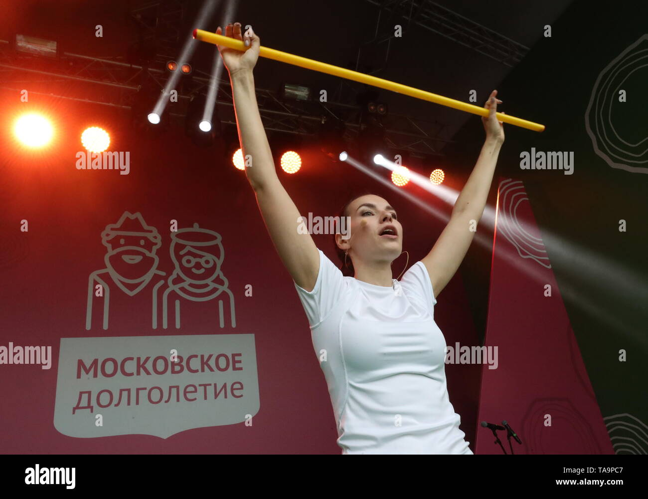 Moscow, Russia. 23rd May, 2019. MOSCOW, RUSSIA - MAY 23, 2019: A coach of the Moscow Longevity project seen as senior citizens set a world record of 'the most populous exercise with sticks' among people of older age, at the opening of a summer season at Moscow's Muzeon Park. Sergei Savostyanov/TASS Credit: ITAR-TASS News Agency/Alamy Live News - Stock Image