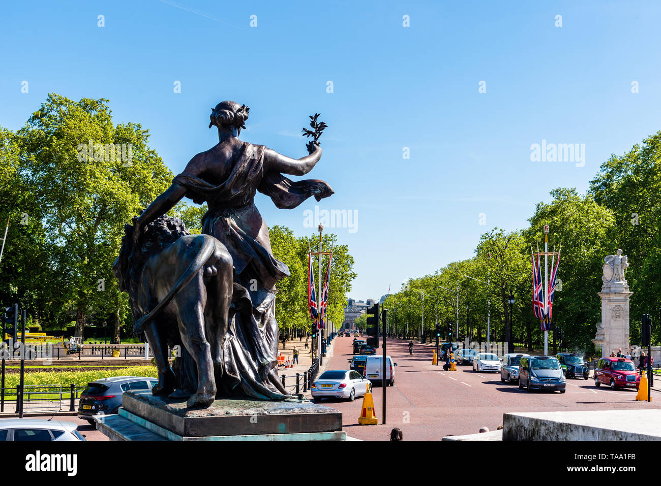 London, UK - May 14, 2019:  Victoria Memorial Sculpture in front of Buckingham Palace a sunny day against The Mall Road Stock Photo
