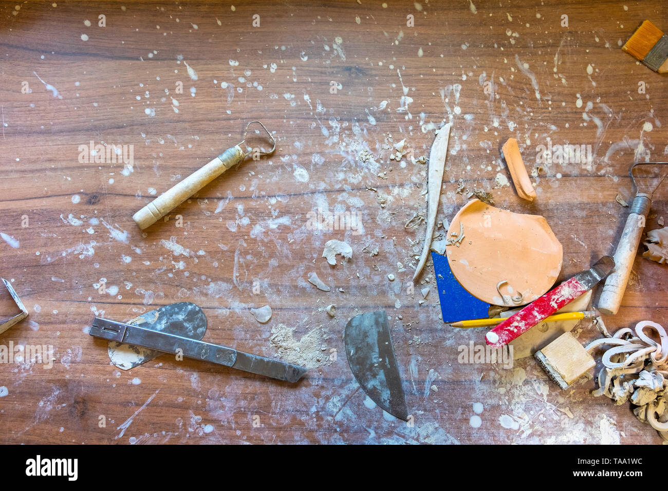 Creative mess on the wooden desk in pottery workshop - Stock Image