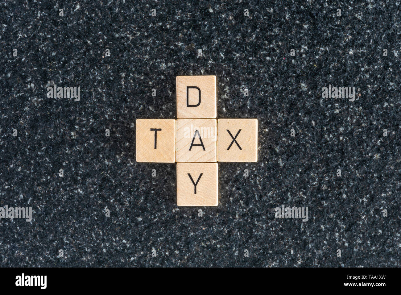 Wood letters forming tax day cross on a black table background. The deadline to pay taxes. - Stock Image