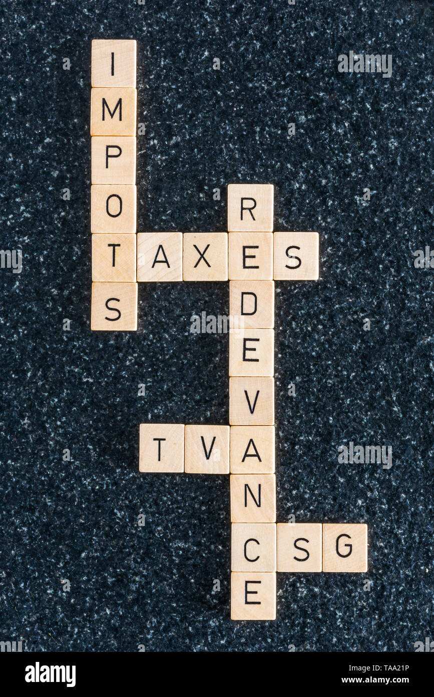 Wood letters forming french various tax names on a black table - Stock Image