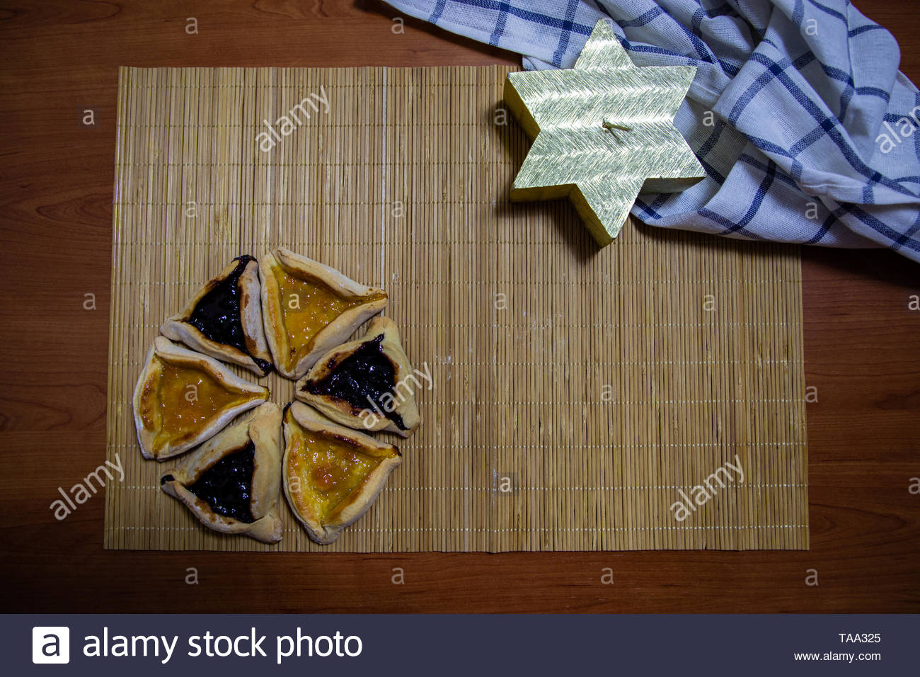 Hamantash Purim blueberry and apricot jam cookies with wooden table background and David star shape candle - Stock Image