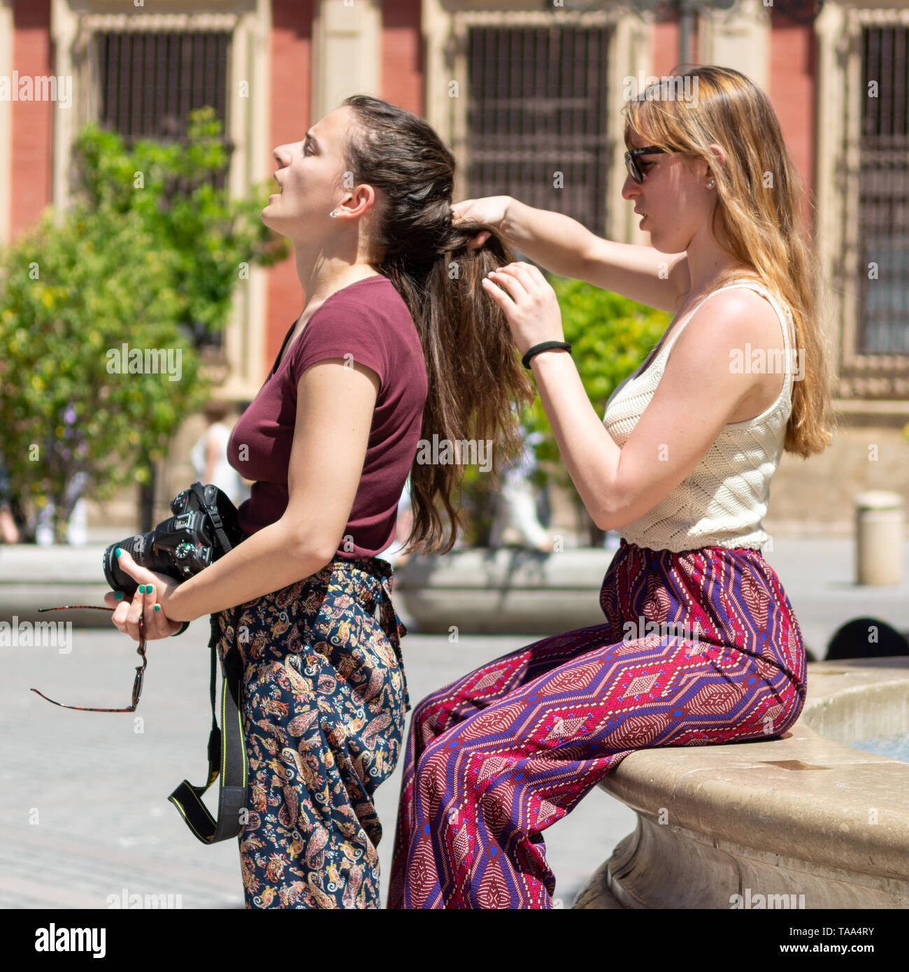 Girl plaiting hair for a friend in a public space on a hot day. - Stock Image