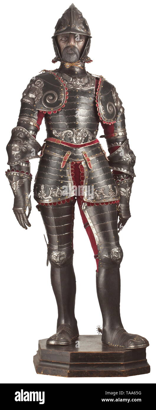 An embossed armour alla romana in the style of circa 1540, in the manner of Caremolo Modrone of mantua, partly 19th century Embossed throughout with mannerist designs of scrolling acanthus and volutes, involving grotesque masks and with a pair of large demon masks centrally over the spauldrons, comprising burgonet with one-piece skull, each side with a voluted scroll developing in a spray of acanthus swept over the brow and diminishing towards the nape, pointed peak and neck guard, a pair of hinged cheekpieces (associated) and with recessed borde, Additional-Rights-Clearance-Info-Not-Available - Stock Image