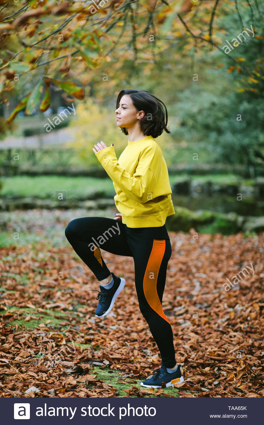 Sporty woman running in place at city park in autumn. Female athlete exercising outdoor. - Stock Image