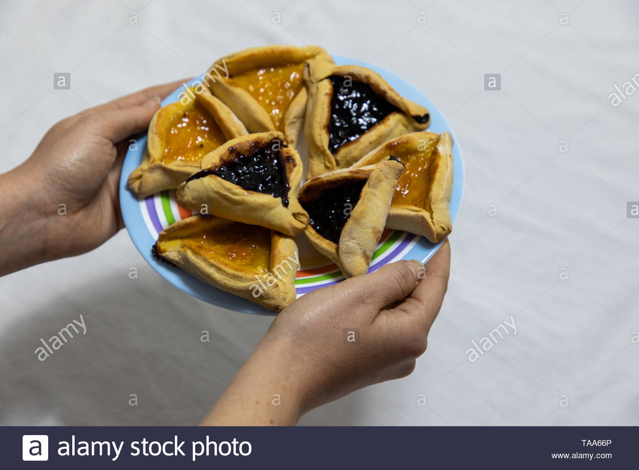 Woman hands holding colorful plate with apricot and blueberry hamantash Purim cookies - Stock Image