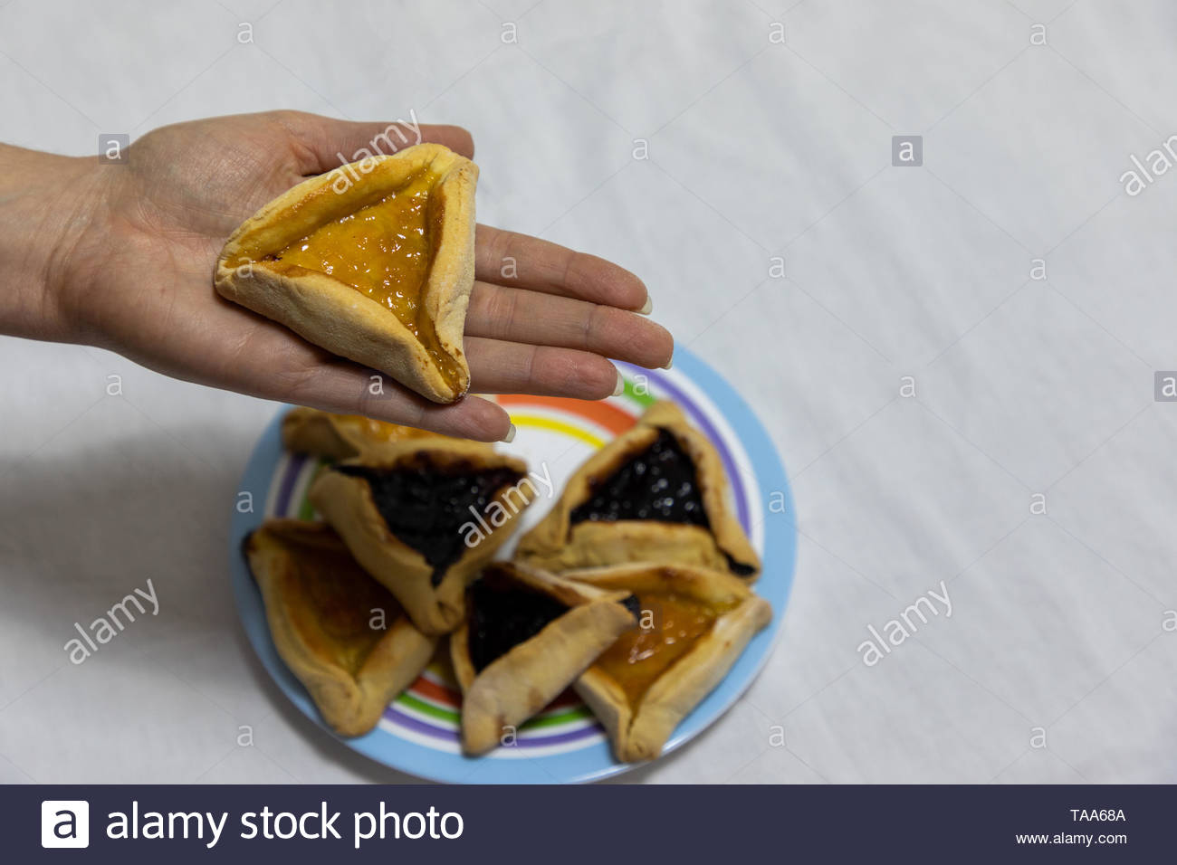 Woman hand holding hamantash cookie on top of colorful plate with more hamantash cookies - Stock Image