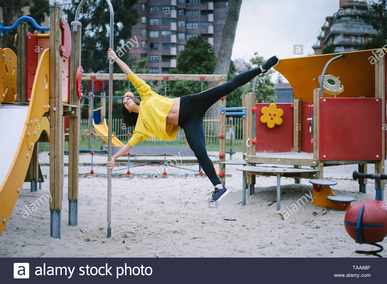 Strong fit woman doing calisthenics exercise in city park. - Stock Image