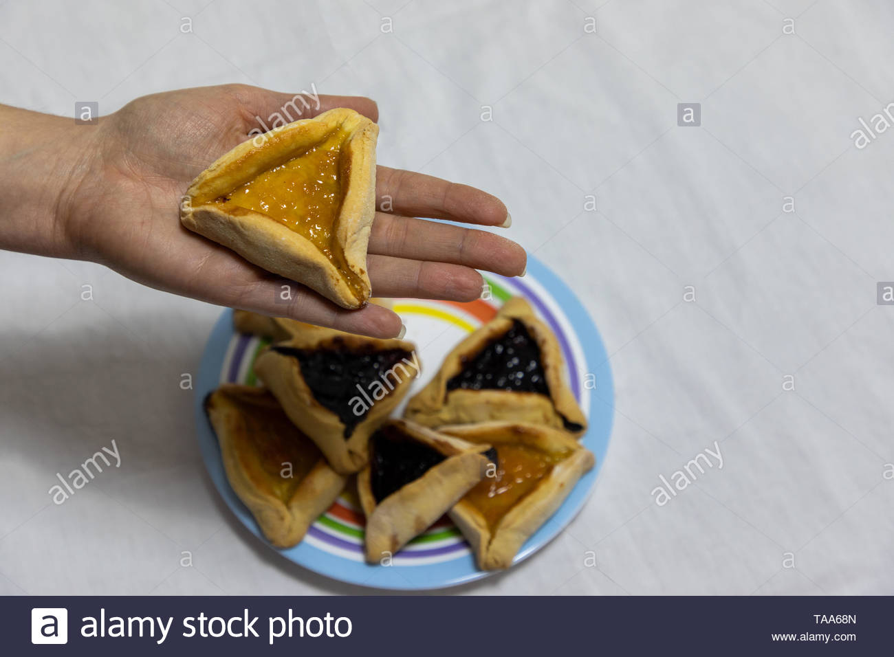 Woman hand holding hamantash cookie on top of colorful plate with more hamantash cookies Stock Photo