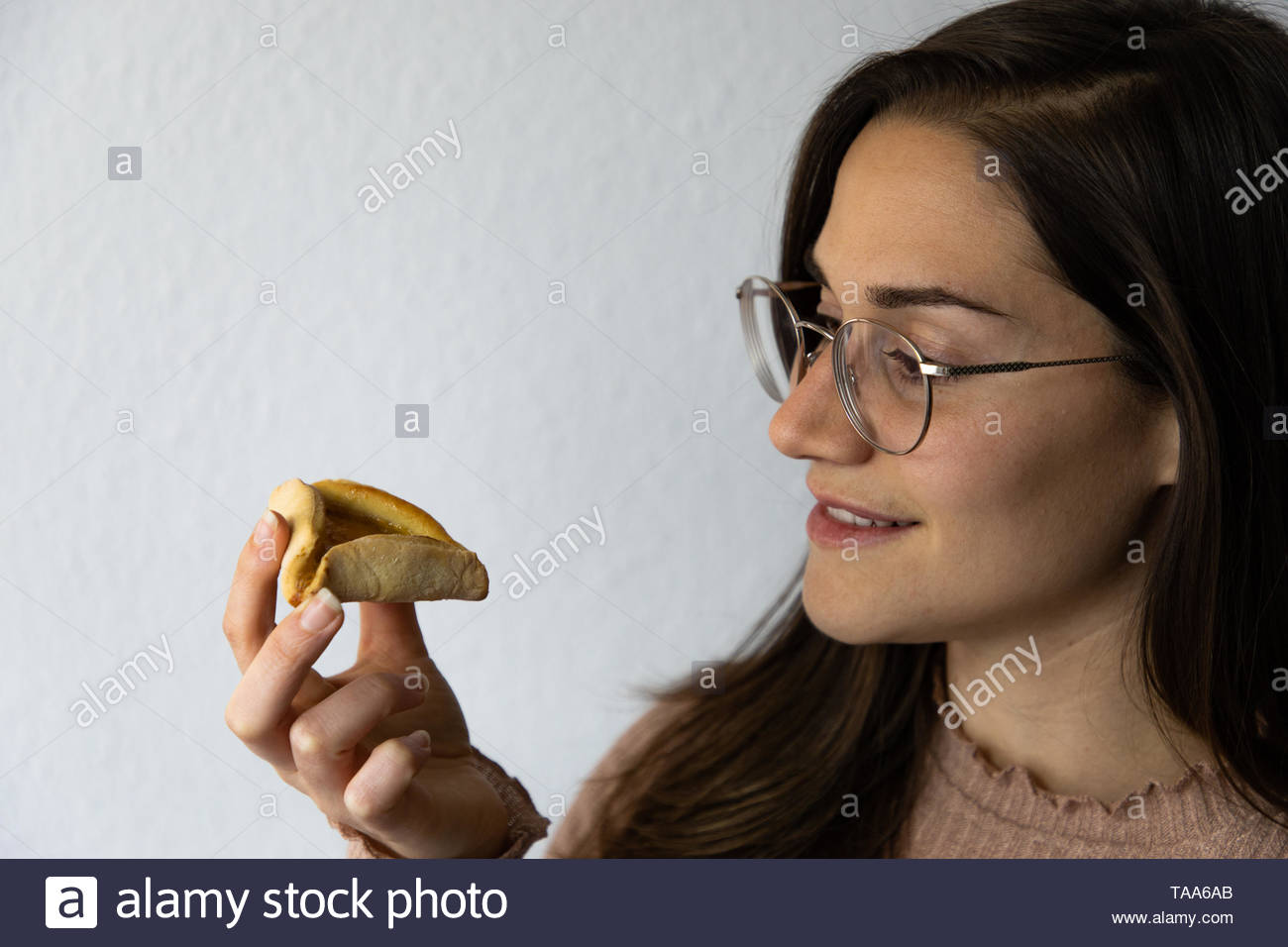 Beautiful and happy women portrait eating hamantash Purim apricot cookie Stock Photo