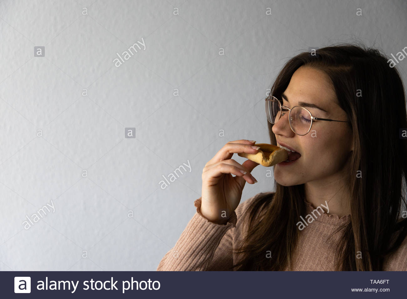 Beautiful and happy women portrait eating hamantash Purim apricot cookie - Stock Image