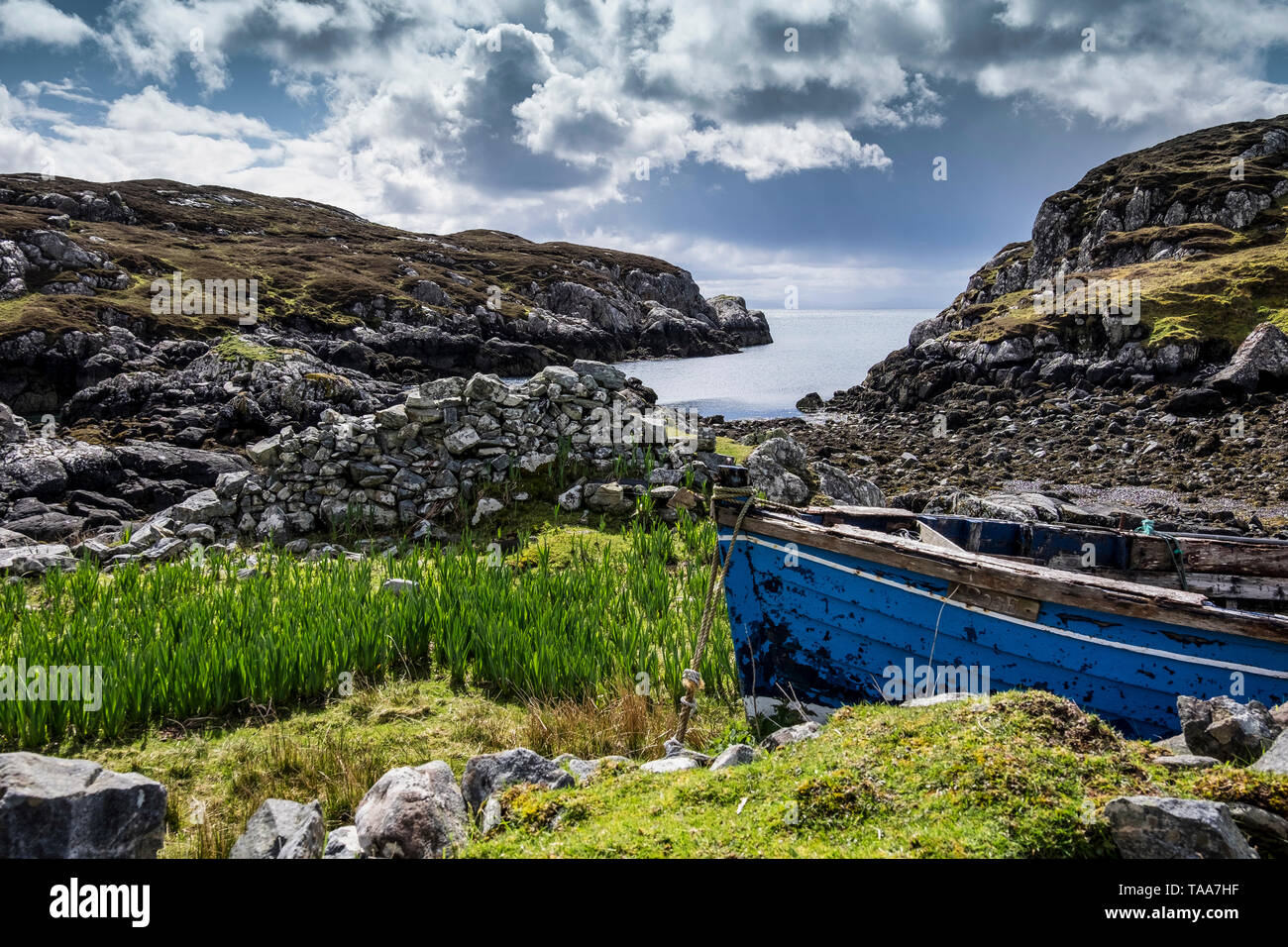 Dramatic light with crofters clinker-built fishing boat, Lingerbay, Harris - Stock Image