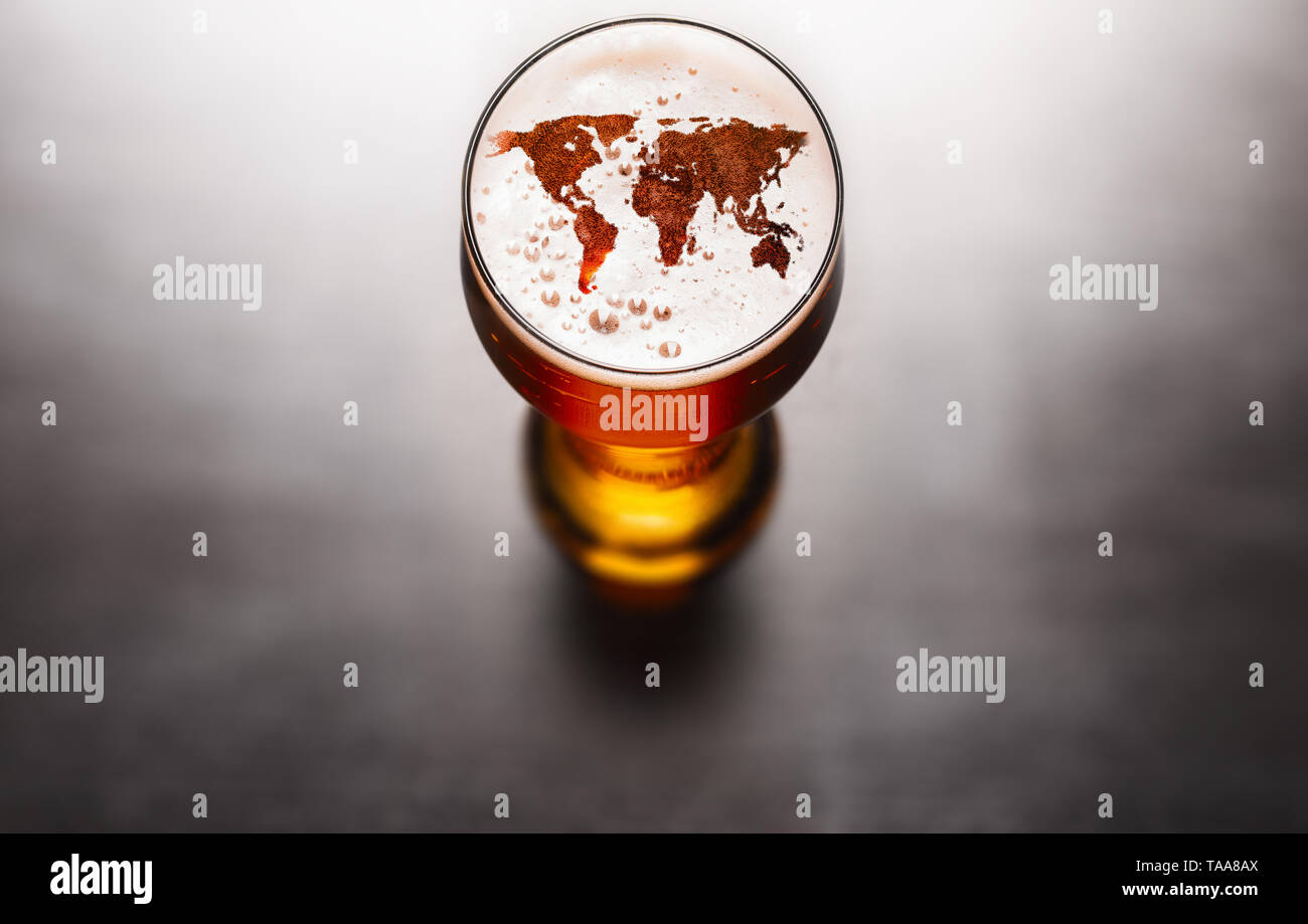 world map silhouette on foam in beer glass on black table. The continents shapes are altered ones from visibleearth.nasa.gov - Stock Image
